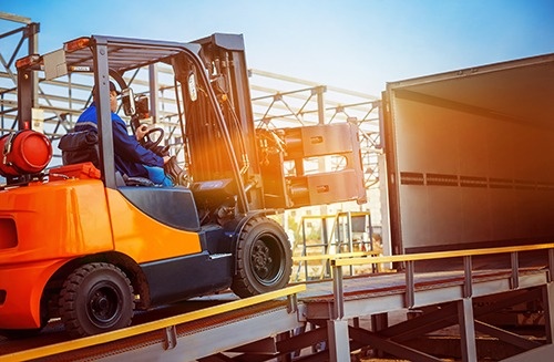 Forklift is putting cargo from warehouse to truck outdoors